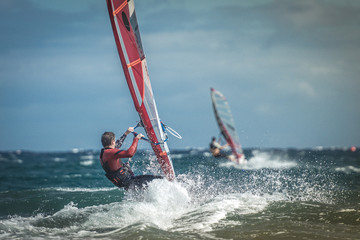 Surfer riding waves in a beautiful sunny day. Young man enjoying the wind and the ocean surfing in Tenerife island. Sea wave and surfers on the sea. Windsurfing, fun among the waves, extreme sport