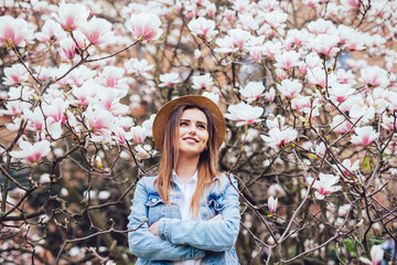 Happy beautiful young woman in spring blossom park with magnolia trees.