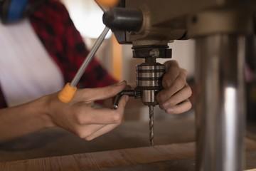 Female welder checking vertical drilling machine