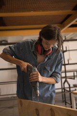 Young woman using using drilling machine in workshop