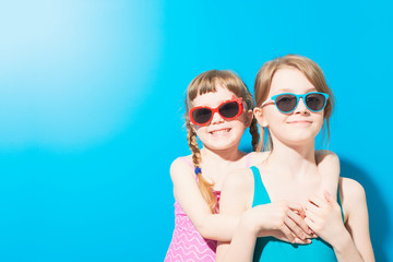 Cute girls in swimwear with glasses hugging on blue background