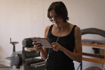 Female welder using digital tablet in workshop