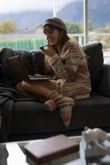 Woman using laptop while talking on mobile phone in living room