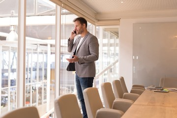 Businessman talking on mobile phone in conference room
