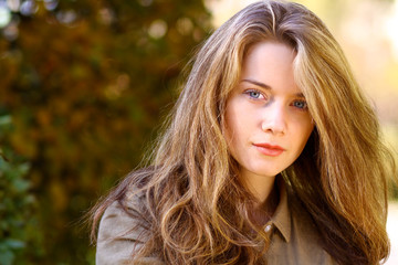Portrait of beautiful young woman with blonde hair in autumn