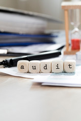 Word AUDIT composed of wooden letters. Closeup
