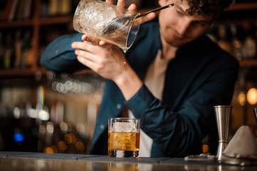 barman finishes preparing an alcoholic cocktail Old Fashioned