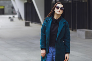 Beautiful brunette girl. Fashionable, stylish with black hair, in a coat and jeans