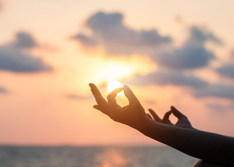 Mantra yoga meditation practice with silhouette of woman in lotus pose having peaceful mind relaxation on the beach outdoor training with sunset golden hour heavenly sky