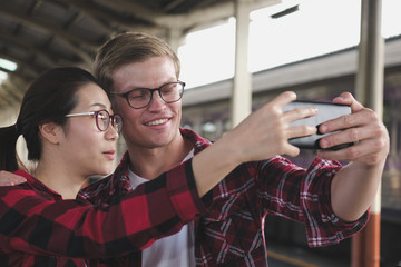 man & woman use smart phone to take selfie photo at train station. traveler couple travel together on holiday