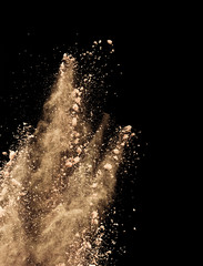Abstract colored brown powder explosion isolated on black background.