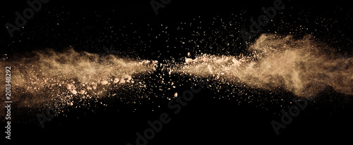 Fototapete Abstract colored brown powder explosion isolated on black background.