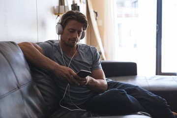 Man using mobile phone with headphones in living room