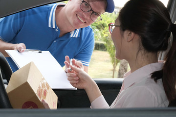 woman on car signing signature on clipboard to receive package from delivery man. male postal courier person deliver box