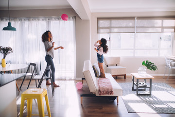 african mother and daughter playing with balloon in living room