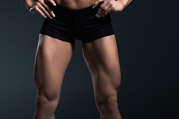 cropped view of female bodybuilders legs, isolated on grey