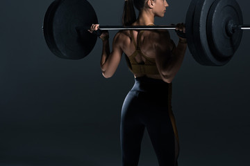 back view of female bodybuilder posing with barbell, isolated on grey