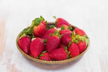 strawberries in dish on ceramic background