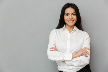 Portrait of caucasian woman with long brown hair wearing office clothing smiling at camera while posing with arms folded, isolated over gray background
