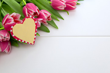 Mother's Day card and a bouquet of beautiful tulips on wooden background.