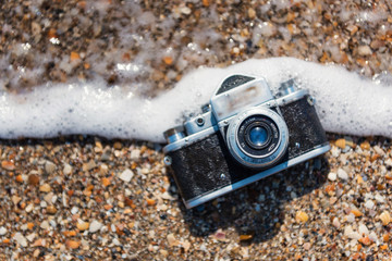 Retro photo camera in the water on the beach, sinks in sea foam. Close-up photo.