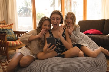 Siblings waving during video call on smartphone at home