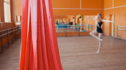 Red silk in front of young woman training a gymnastics exercise with a ribbon