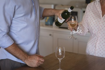 Man pouring champagne into glass at home