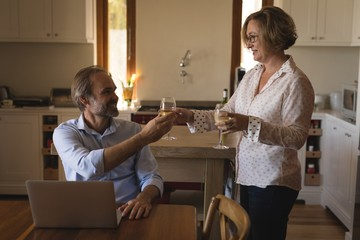 Couple having champagne in kitchen