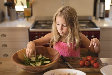 Girl preparing salad with cucumbers and tomatoes in kitchen at home