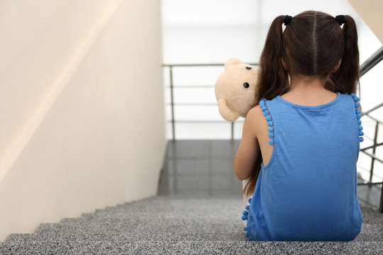 Lonely little girl sitting on stairs. Autism concept