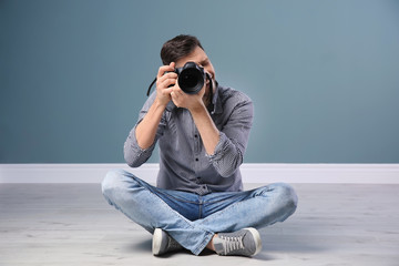 Male photographer with camera near grey wall
