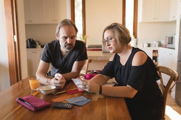 Couple calculating invoice bills in kitchen