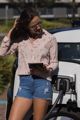Woman using digital tablet while charging electric car