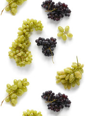 Black and green grapes isolated on a white background. The pattern of grapes of different varieties, top view. Food background.