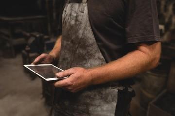 Blacksmith using digital tablet in workshop
