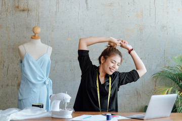 Young designer stretching herself while work in studio, work lifestyle concept.