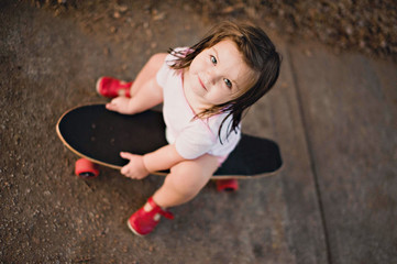 Overhead view of a Girl sitting on a skateboard