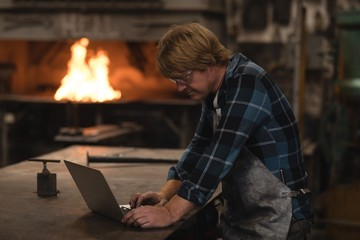 Blacksmith using laptop in workshop