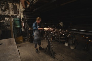 Blacksmith grinding a metal rod with grinder machine