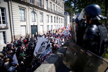 French gendarmes watch as protesters attend a demonstration against the French government's reform plans in Nantes