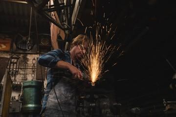 Blacksmith grinding a metal rod with grinder machine