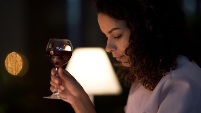 Biracial woman drinking wine in small restaurant, typing message on smartphone