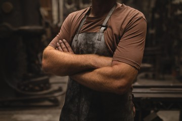 Blacksmith standing with arms crossed in workshop