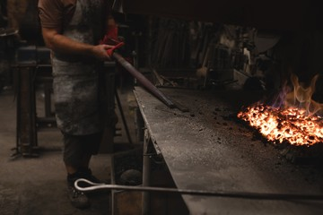 Blacksmith heating metal rod in fire