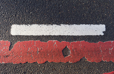 Roads: Worn road marking between cycle path and roadway on a damp inner-city asphalt road