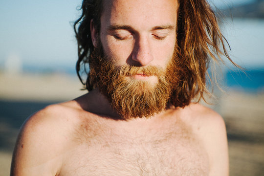 Portrait of a man with long hair and a beard standing on beach