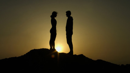 Couple on top of hill against sunset, fateful meeting on edge of earth, love