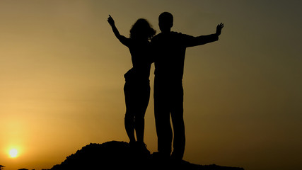 Silhouette of happy couple enjoying sunset together, looking in future with hope