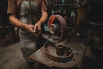 Blacksmith shaping a metal rod